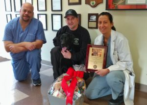 Doctors, trained dog, and handler pose with award and gift basket