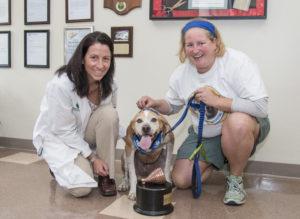 Doctor, pet owner, and award-winning dog smile for camera